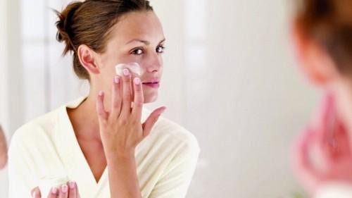 женщина защищает кожу лица кремом
